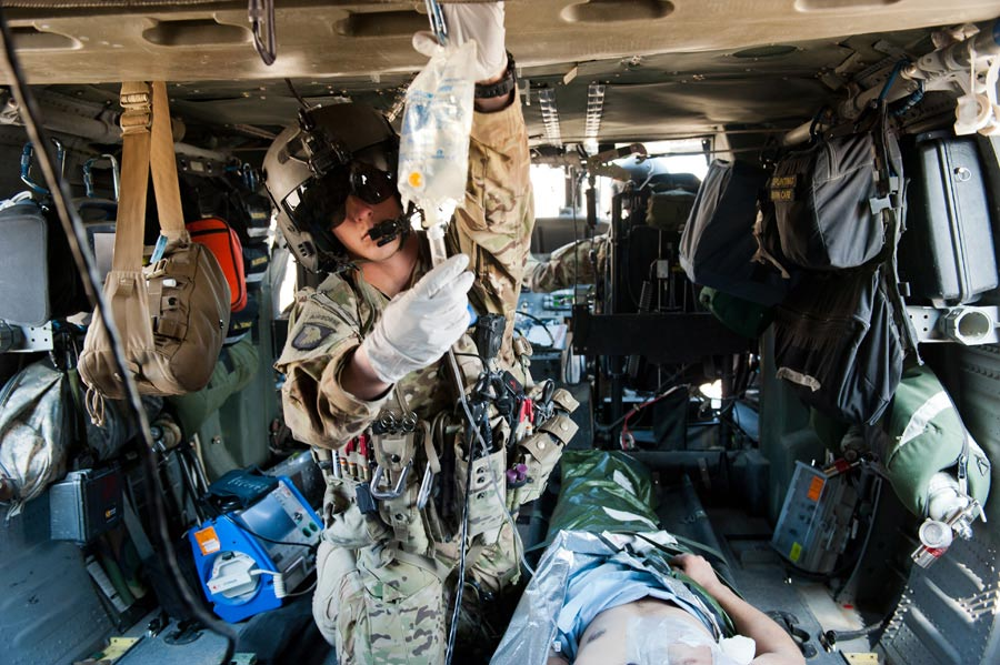 Specialist Thomas Appelhanz, flight medic with 101st Combat Aviation Brigade, checks on IV fluid of wounded Afghan National Army Soldier during patient transfer mission