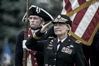 General Ann E. Dunwoody salutes during playing of national anthem at her retirement ceremony