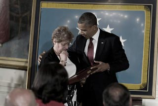 Rose Mary Brown, widow of Specialist Leslie H. Sabo Jr., accepts Sabo's Medal of Honor from President Obama