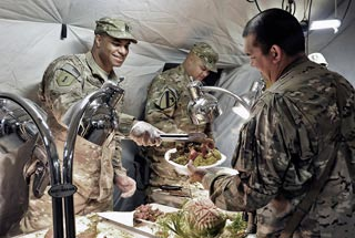Captain Jefferson Mason, left, serves Thanksgiving dinner to a Soldier on Joint Combat Outpost Mushan, Afghanistan